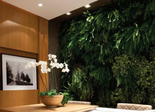 jardim vertical na sala : jardim vertical na sala:Jardim Vertical: Na sala de jantar, a área recuada atrás da mesa